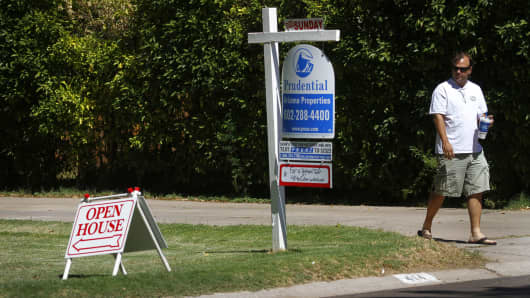 A prospective home buyer walks past real estate signs outside of a property during an open house in Phoenix, Arizona.