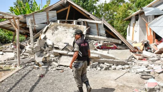 An Indonesian village security officer examines the remains of houses, after a 6.4 magnitude earthquake struck, in Lombok on July 29, 2018.