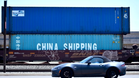 A motorist drives past shipping containers, including one from China Shipping, awaiting transportation at the Port of Long Beach on July 12, 2018 in Long Beach, California.