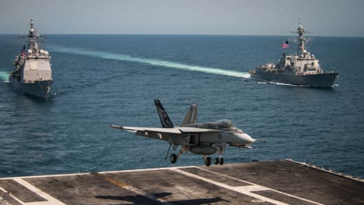 In this handout provided by the U.S. Navy, an F/A-18E Super Hornet from the Kestrels of Strike Fighter Squadron (VFA) 137 lands on the flight deck of the Nimitz-class aircraft carrier USS Carl Vinson (CVN 70) as the Ticonderoga-class guided-missile cruiser USS Lake Champlain (CG 57) and the Arleigh Burke-class guided-missile destroyer USS Wayne E. Meyer (DDG 108) accompany May 3, 2017 in the western Pacific Ocean.