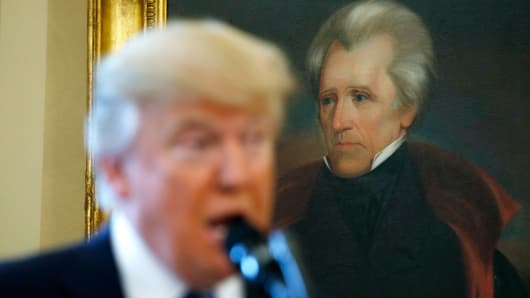 President Donald Trump speaks in front of a portrait of former U.S. President Andrew Jackson in the Oval Office.