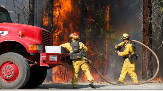 Firefighters with CalFire's Shasta-Trinity Unit extinguish flames near State Highway 299 while battling the Carr Fire on July 30, 2018 near Redding, California.