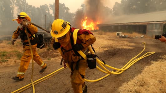 West Covina firefighters pulls hose away from a horse barn that burns as the River Fire moves through the area on July 31, 2018 in Lakeport, California.