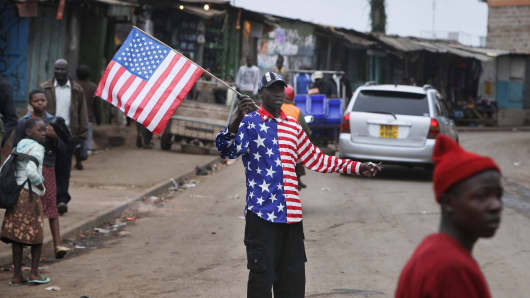 A man waves an US flag in Kibera neighbourhood, Nairobi on July 25, 2015.PHOTO/Till Muellenmeister        (Photo credit should read Till Muellenmeister/AFP/Getty Images)