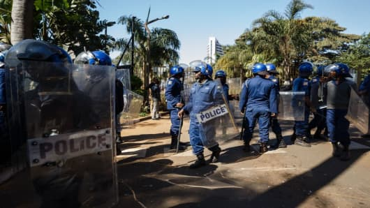 Zimbabwe police barricade with water canons the entrance to the Rainbow Towers Hotel where the country's electoral commission (ZEC) announced the results of the general election on August 1, 2018.