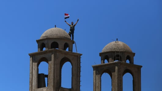 A Syrian soldier waves the national flag atop the Greek Orthodox Church of St. George in the town of Quneitra in the Syrian Golan Heights on July 27, 2018. - The town was almost completely destroyed by departing Israeli soldiers in 1974 after seven years of occupation.
