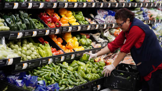 A Walmart associate restocks fresh vegetables  at a Walmart Supercenter in Rogers, Arkansas.
