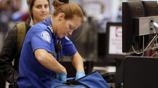A Transportation Security Administration officer checks a traveler's bag at a screening location at Salt Lake City International Airport.