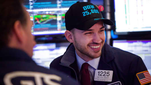 A trader wears a 'Dow 25,000' hat while working works on the floor of the New York Stock Exchange (NYSE) in New York, Jan. 4, 2018.