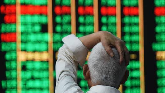 2 июля 2018 года инвестор наблюдает за электронной доской на фондовой бирже в Ханчжоу, Китай.