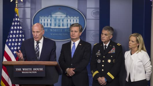 Dan Coats, director of national intelligence, from left, speaks as Christopher Wray, director of the Federal Bureau of Investigation (FBI), Paul Nakasone, director of the National Security Agency (NSA) and commander of the U.S. Cyber Command, and Kirstjen Nielsen, U.S. secretary of Homeland Security (DHS), listen during a White House press briefing in Washington, D.C., U.S., on Thursday, Aug. 2, 2018.