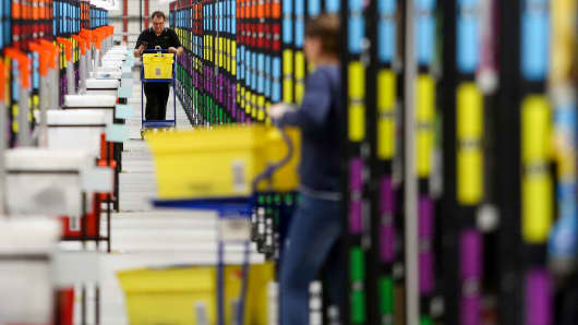 An employee pushes a trolley along an aisle at the Amazon.com Inc. fulfillment center in Hemel Hempstead, U.K.