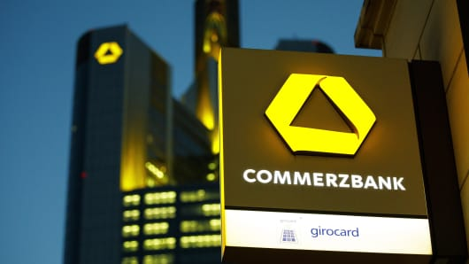 The Commerzbank AG logo sits on an illuminated sign outside a bank branch as the bank's headquarters stand beyond at dusk in Frankfurt, Germany, on Monday, Feb. 5, 2017.