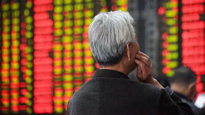 An investor looks at an electronic board showing stock information at a brokerage house in Nanjing, Jiangsu province, China.