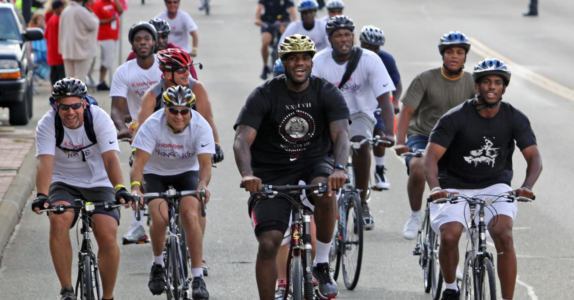 LeBron James and Chris Paul ride their bikes at the LeBron James State Farm King For Kids Bike-a-thon in Akron, Ohio