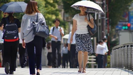 Pedestrians walk along a street during in Tokyo on August 2, 2018.