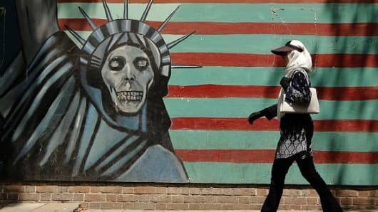 An Iranian woman walks by a mural painting on the wall of the former US embassy in the Iranian capital Tehran on August 7, 2018.