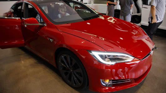 Customers view a Tesla Inc. Model S electric vehicle on display at the company's showroom in Newport Beach, California, U.S., on Friday, July 6, 2018. Tesla Inc. reached a milestone critical to Elon Musk's goal to bring electric cars to the masses -- and earn some profit in the process -- by finally exceeding a long-sought production target with the Model 3. Photographer: Patrick T. Fallon/Bloomberg via Getty Images