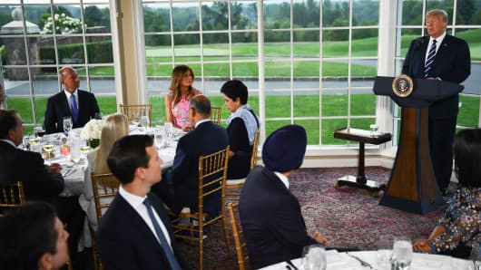 President Donald Trump (R) speaks, flanked by First Lady Melania Trump (2nd L), Boeing CEO Dennis Muilenburg (L) and CEO of PepsiCo Indra Nooyi (3rd L), during a dinner with business leaders in Bedminster, New Jersey, on August 7, 2018.