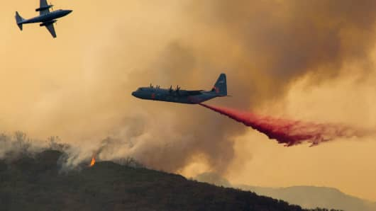 A U.S. Airforce C-130 Hercules drops fire retardant at the Holy Fire near Lake Elsinore, in Orange County, California, on August 7, 2018.