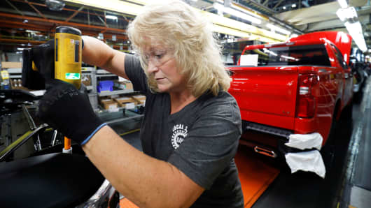 Kathy Huff installs a headlight assembly at GM's Chevrolet Silverado and GMC Sierra pickup truck plant in Fort Wayne, Indiana, July 25, 2018.