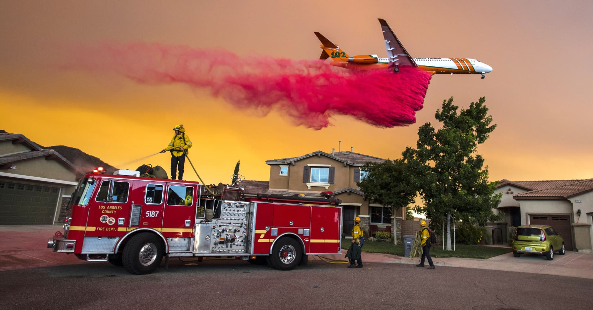 A plane drops fire retardant behind homes along McVicker Canyon Park Road in Lake Elsinore, Calif., as the Holy Fire burned near homes on Wednesday, Aug. 8, 2018.