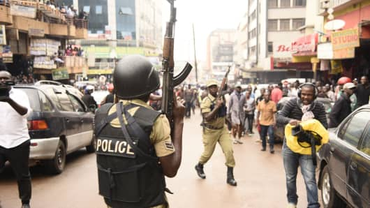 Ugandan police officers are seen lifting their AK-47 rifles opposite protesters during a demonstration on July 11, 2018, in the capital Kampala. The protest is against a controverial tax on social media.
