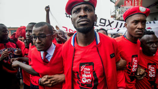Musician turned politician Robert Kyagulanyi (C) is joined by other activists in the Ugandan capital of Kampala on July 11, 2018, during a demonstration to protest against a tax on social media use.