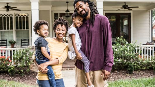 Portrait of family in front of suburban home