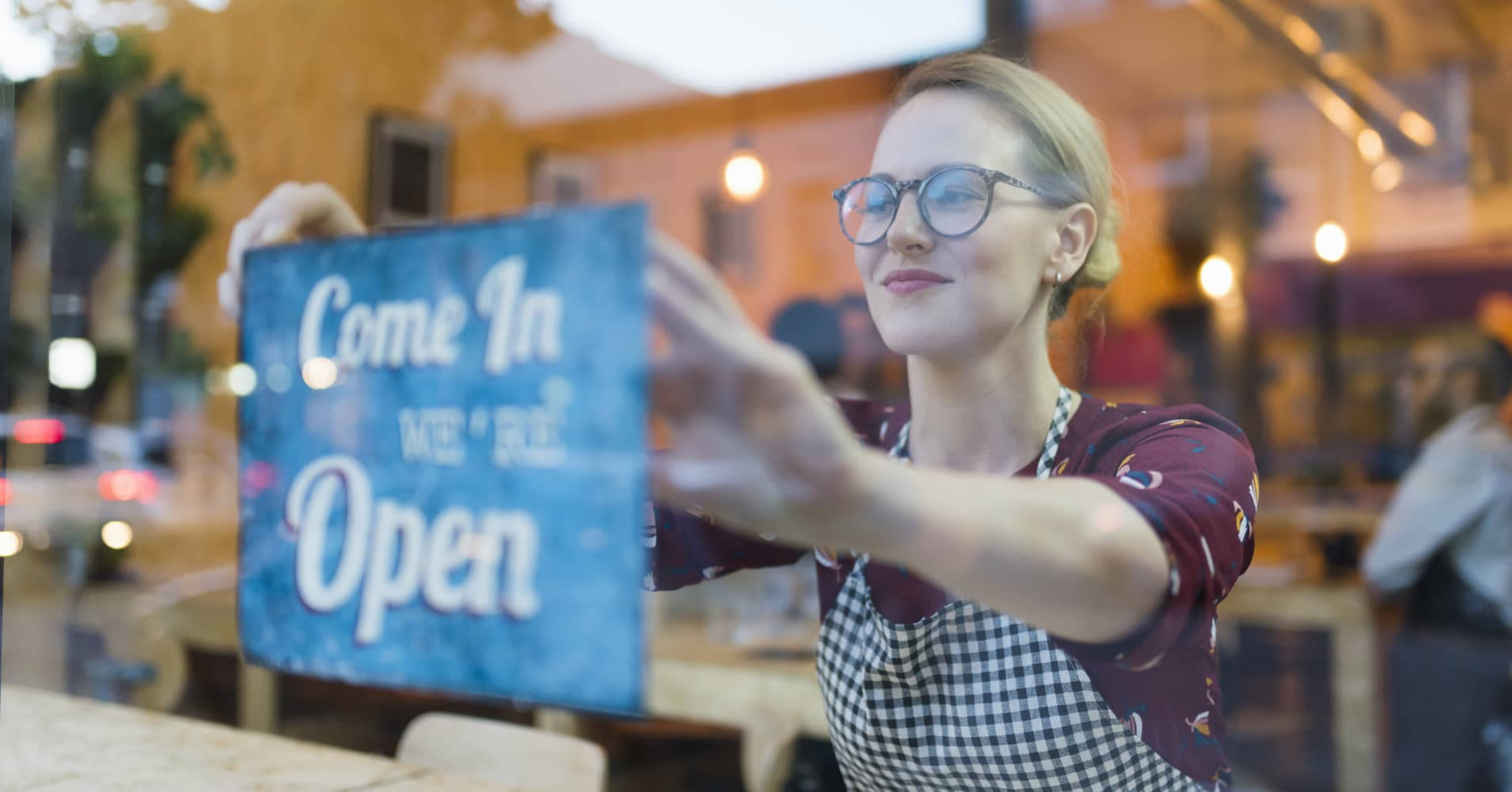 Business owner setting up open sign in cafe window