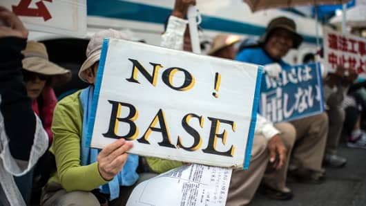 Protesters hold placards at an earlier demonstration against a United States military base in Okinawa prefecture, Japan.