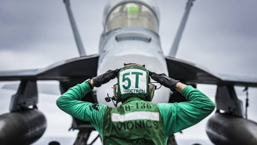 U.S. Navy Aviation Electronics Technician signals to the crew of an EA-18G Growler on the flight deck of aircraft carrier USS Carl Vinson.