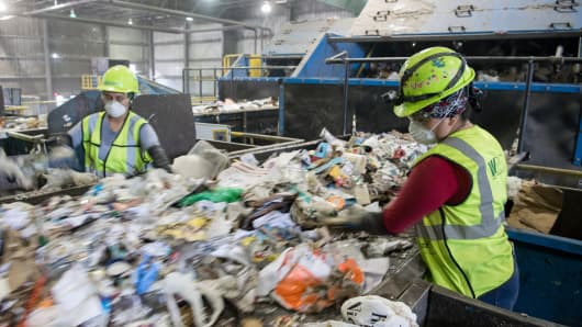 Workers sort recycling material at the Waste Management Material Recovery Facility in Elkridge, Maryland, June 28, 2018.