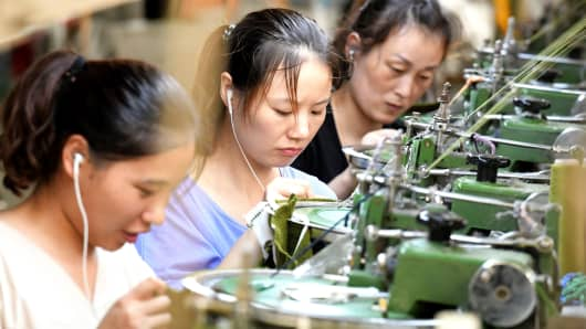 Employees working on a production line of clothes for export at a factory in Xiayi county, in Shangqiu in China's central Henan province.