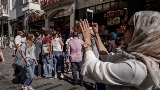 A tourist takes a photograph on an iPhone near a foreign currency exchange store, center, in Istanbul, Turkey, on Monday, Aug. 13, 2018.