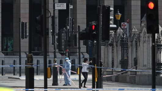 Police forensics officers work in Parliament Square, opposite the Houses of Parliament in central London on August 14, 2018, where a car was driven into the barriers.