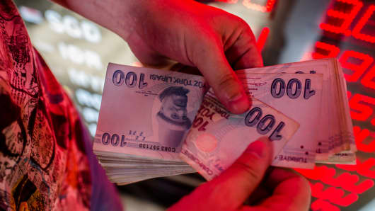 A money changer counts Turkish lira banknotes at a currency exchange office in Istanbul, on August 8, 2018.