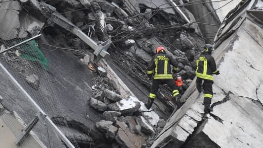 Rescuers at work amid the rubble after a highway bridge collapsed in Genoa, Italy, 14 August 2018. A large section of the Morandi viaduct upon which the A10 motorway runs collapsed in Genoa on Tuesday.