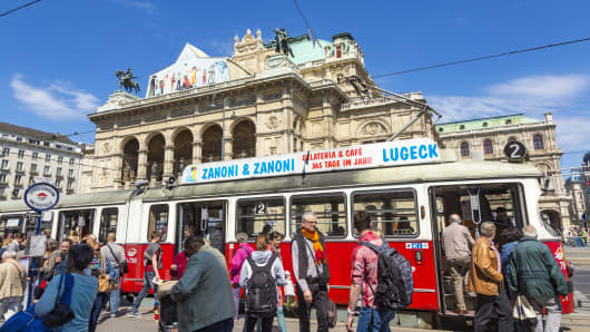 People board a streetcar in front of Vienna State Opera house. the Hofburg, in Vienna, Austria.