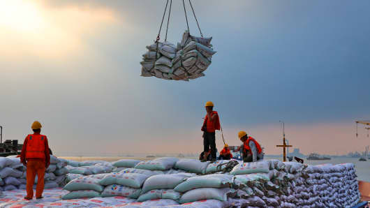 Workers transport bags of soybean meal in a dockyard in Nantong in east China's Jiangsu province on Aug. 06, 2018.