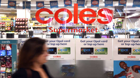 A woman walks past a Coles supermarket in Sydney's central business district on March 16, 2018. Australian supermarket chain Coles will be spun off into a separate entity by owner Wesfarmers, the company said on Friday, amid a shake-up in the food retail sector as new entrants threaten a longstanding duopoly. Coles, which together with rival Woolworths is one of Australia's two main supermarket giants, will become one of the nation's 30 biggest listed firms after the demerger, conglomerate Wesfarmers said.