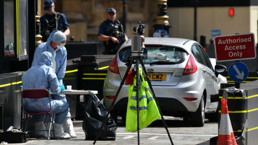 Forensic officers look towards a vehicle after it crashed into security barriers, injuring a number of pedestrians, outside the Houses of Parliament on August 14, 2018, in London, England.