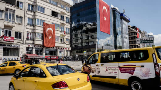 Yellow cabs sit at a taxi rank near buildings decorated with Turkish national flags in Istanbul, Turkey, on Tuesday, July 19, 2016.