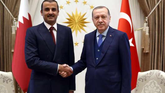 Turkish President Recep Tayyip Erdogan (R) and Emir of Qatar Sheikh Tamim bin Hamad Al Thani (L) shake hands as they pose for a photo during their meeting at Presidential Complex in Ankara, Turkey on January 15, 2018.