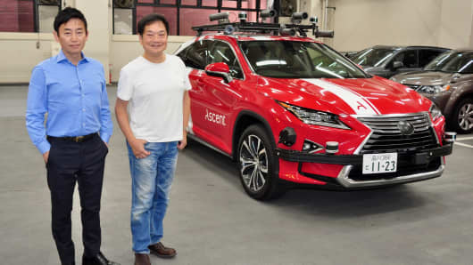 Ascent Robotics CEO Davey Ishizaki (left) and board member Ken Kutaragi pose with one of the company's self-driving Lexus hybrid SUVs in Tokyo.