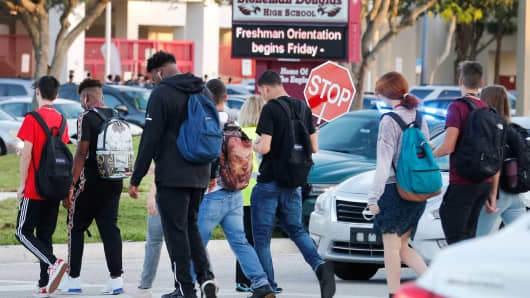 Students cross a street to enter for the first day of classes at Marjory Stoneman Douglas High School in Parkland, Florida, August 15, 2018.