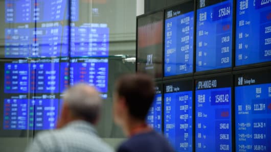 Visitors look at screens displaying stock indices at the Tokyo Stock Exchange in Tokyo, Japan, on Tuesday, July 24, 2018.