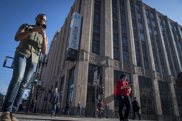 Pedestrians use mobile phones while walking past Twitter Inc. headquarters in San Francisco, California, U.S.