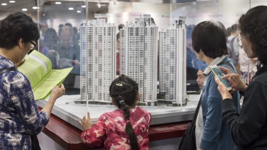 Applicants looking at housing models in an application center in Hong Kong.