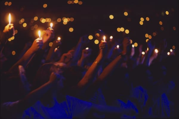 People holding lighters at a concert circa 2000.
